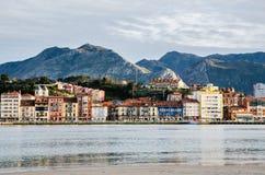 里瓦德塞利亚,阿斯图里亚斯 出海口、五颜六色的大厦和山在背景中在日落期间 免版税库存照片