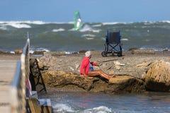 里窝那,意大利- 2017年8月:年长妇女坐岩石和她的轮椅 免版税库存图片