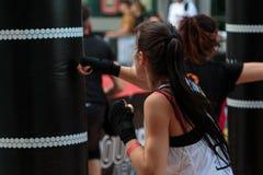 里米尼,意大利-可以2016年:有短裤和白色无袖衫的女孩:健身与沙袋的拳击锻炼 库存图片