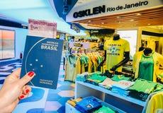 里约热内卢,巴西- 2017年8月27日, :持与里面5雷亚尔笔记的手的社论例证一本巴西护照 库存照片