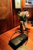 里面地方小狗-手机,万一和在盐和胡椒罐和小花瓶的放大镜花旁边 免版税图库摄影