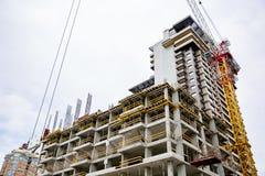 里面建筑工地建设中和起重机有蓝天背景 在建造场所的未完成的水泥大厦 库存图片