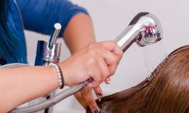 里面理发交谊厅,妇女递洗有冷水的一根长的头发 免版税库存图片