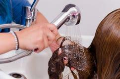 里面理发交谊厅,妇女递洗有冷水的一根长的头发 免版税库存照片