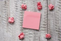 重套与小块的简单的便条纸在木织地不很细桌上 桃红色空白纸和在仿造上破坏 库存图片