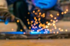 重工业焊工工作者在拿着电弧焊接火炬的防毒面具手上运作在金属建筑 库存图片