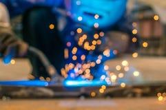 重工业焊工工作者在拿着电弧焊接火炬的防毒面具手上运作在金属建筑 免版税库存图片