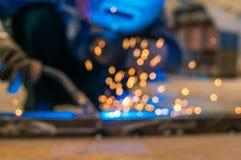 重工业焊工工作者在拿着电弧焊接火炬的防毒面具手上运作在金属建筑 图库摄影