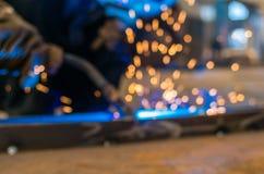 重工业焊工工作者在拿着电弧焊接火炬的防毒面具手上运作在金属建筑 免版税图库摄影