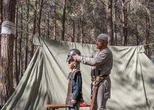 重建`北欧海盗村庄`的参加者在森林里帮助访客佩带在阵营的装甲在本Shemen附近我 免版税库存照片
