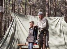 重建`北欧海盗村庄`的参加者在森林里帮助访客佩带在阵营的装甲在本Shemen附近我 免版税图库摄影