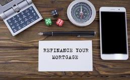 重新贷款在纸、木背景书桌有计算器的,模子、指南针、巧妙的电话和笔写的您的抵押 库存图片