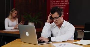 重点在工作 年轻商人在有膝上型计算机的办公室看非常疲乏工作 事务,人们,文书工作和 股票录像