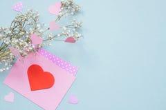重点 与心脏的华伦泰在蓝色背景的卡片和花 复制空间 库存照片