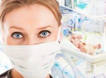 重症监护病房的年轻女性医生与婴儿 库存照片