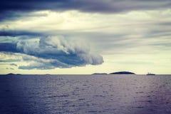 重的云彩、离开的海岛和游艇 免版税库存照片