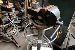 重的产业工人的关闭在金属工作工厂过程运作在执行机械旁边 免版税图库摄影