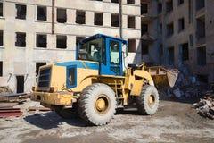 重的前面装载者清除在老居民住房的重建的残骸 免版税库存图片