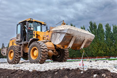 重的推土机装货和移动的石渣在修路站点 库存照片