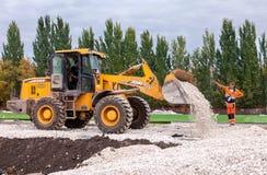 重的推土机装货和移动的石渣在修路站点 库存图片