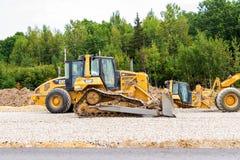 重的推土机装货和移动的石渣在修路 免版税库存照片