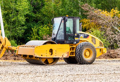 重的推土机装货和移动的石渣在修路 图库摄影
