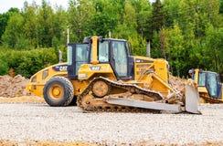 重的推土机装货和移动的石渣在修路 库存图片