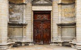 重的木双门在有宗教安心和题字的一个老教会外面 免版税库存照片