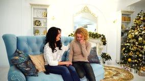 重要支持困难的情况的姐妹 女孩坐长沙发在有壁炉的明亮的客厅 影视素材