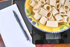 重量控制-与意大利面团、铅笔和报纸的黑玻璃厨房标度 免版税库存图片