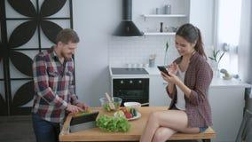 重量正常化,人准备在早餐和妇女的健康素食沙拉坐厨房用桌与 股票录像