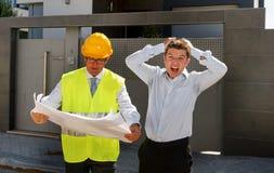 重音和建设者工头工作者的不快乐的顾客有盔甲的和背心争论户外在新房大厦计划 免版税图库摄影