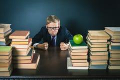 重音或消沉的恼怒的男小学生在学校教室 免版税库存图片