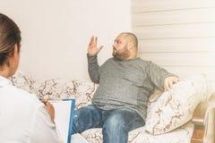 重音的肥胖人情感地告诉关于他的消沉和问题 心理学家咨询 图库摄影