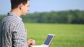 野外工作的白种人男性深色的农夫与膝上型计算机 工作在与农业的领域的科学家 股票视频
