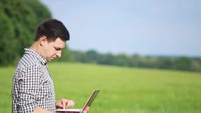 野外工作的白种人男性深色的农夫与膝上型计算机 工作在与农业的领域的科学家 股票录像