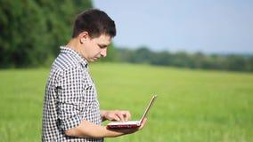野外工作的白种人男性深色的农夫与膝上型计算机 工作在与农业的领域的科学家 影视素材
