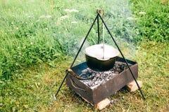野外用的全套炊具 在火的罐 烹调汤户外在山,等待吃 免版税库存图片