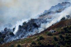 野火往西班牙物产的火焰打扫在Sayalonga和竞技场,安达卢西亚之间 免版税库存照片
