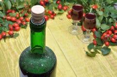野玫瑰果果子和酒客酒在瓶和玻璃 免版税库存图片