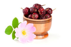 野玫瑰果花用在白色背景隔绝的一个木碗的叶子和野玫瑰果莓果 免版税库存图片