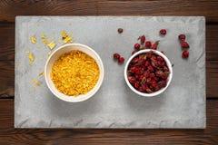 野玫瑰果莓果和医疗草本在一个白色碗在一块混凝土板 木背景 图库摄影