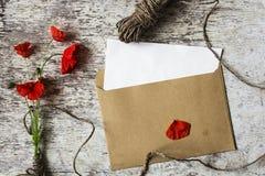 野生红色鸦片花束开花与在白色木背景的信封 免版税库存照片