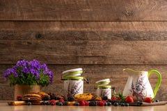 野生莓果、紫罗兰色花、巧克力饼干和陶瓷船的五颜六色的被分类的混合 免版税库存照片