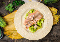 野生鳟鱼用在板材的被炖的黄瓜在老木桌上 免版税库存照片