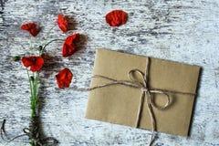 野生鸦片花束开花与在白色葡萄酒木背景的棕色信封 库存照片
