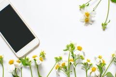 野花和在白色背景隔绝的智能手机装饰 库存图片