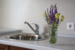 野花小花束在一块玻璃的用水在厨房里 库存图片