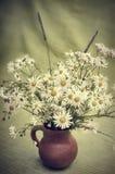 野花花束在泥罐的,定调子 免版税库存图片
