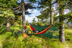 野营与吊床在自行车旅行的夏天森林 库存照片